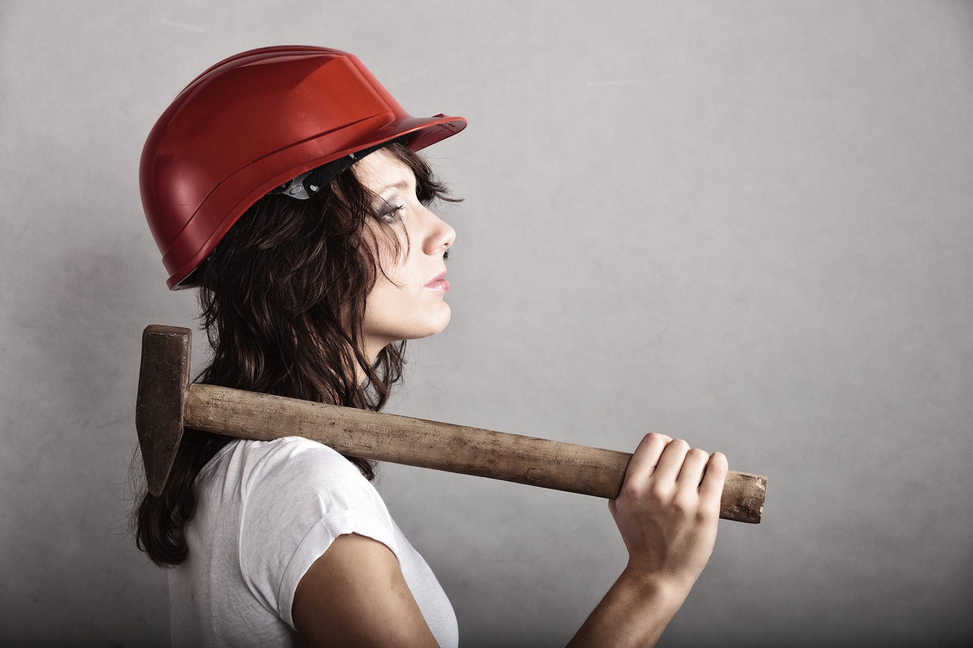 Woman with hard hat and hammer