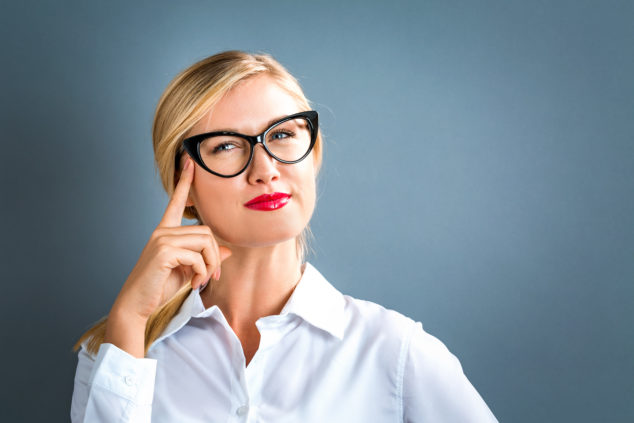 Blonde woman with glasses thinking