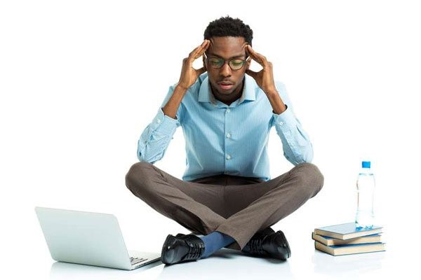 Man sitting on floor with laptop and books